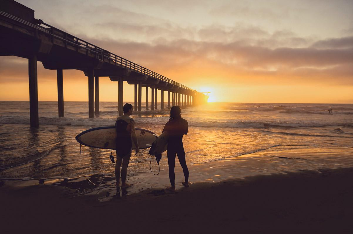 2 surfers watching the sun set next to a pier sunset beach quotes