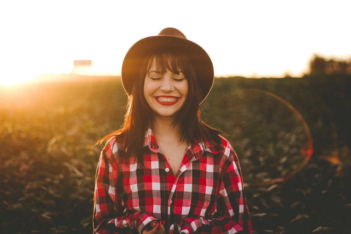 girl smiling and laughing with sun setting funny sunset puns for instagram
