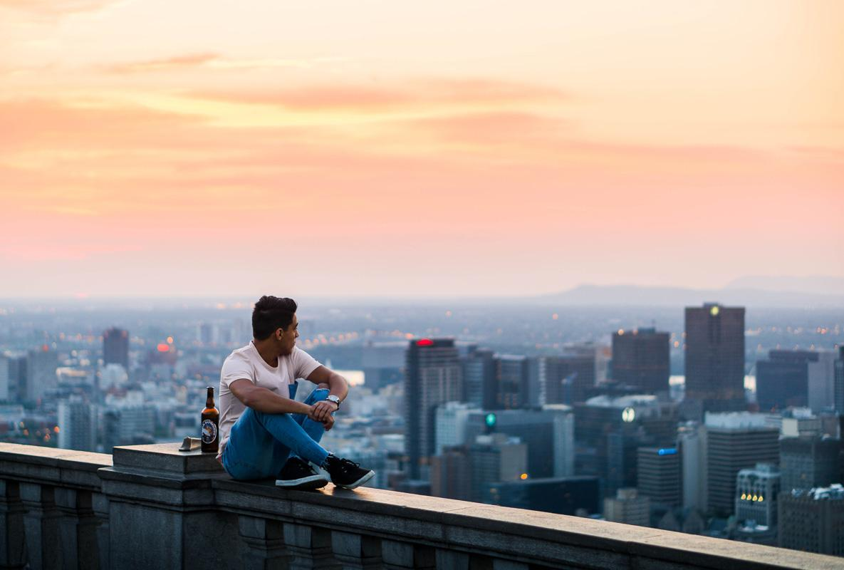 man on balcony looking over the city at sunset motivational sunset quotes