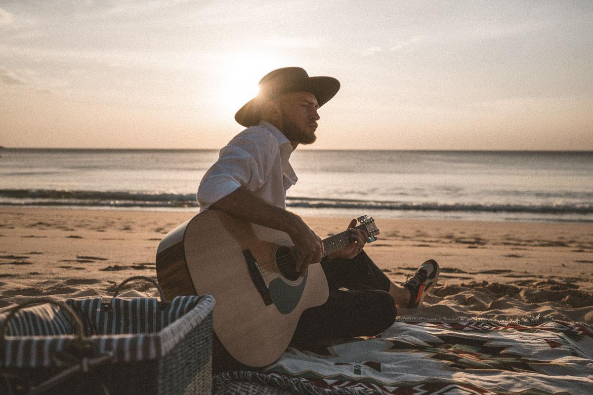 man on the beach at sunset playing guitar sunset song lyrics