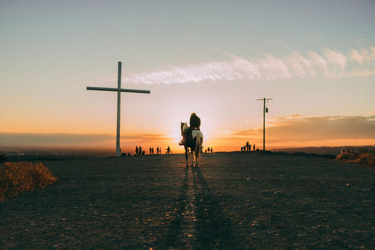 man riding horse in front of cross and sunset quotes on sunset