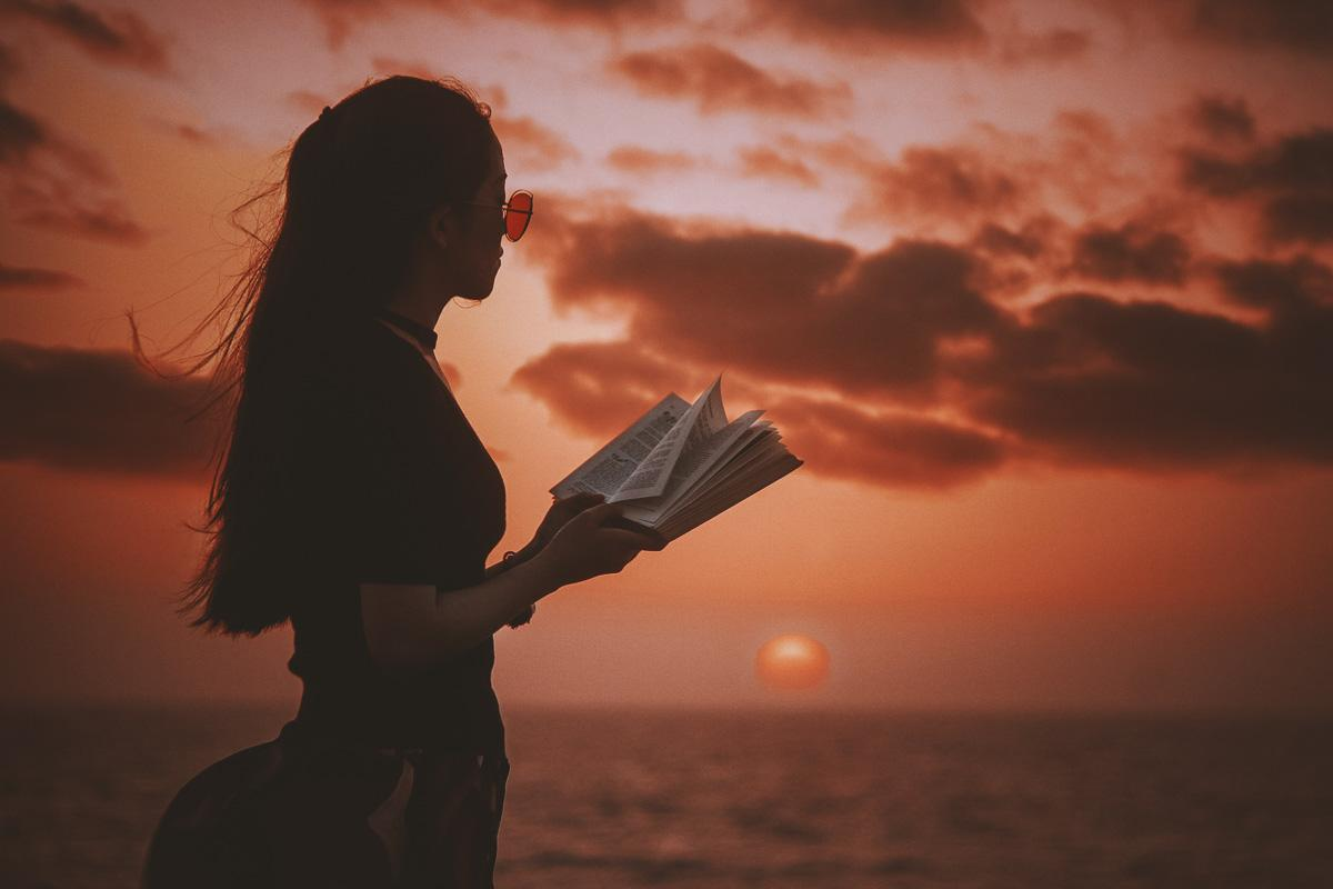 woman reading a book in front of the sunset about sunset quotes
