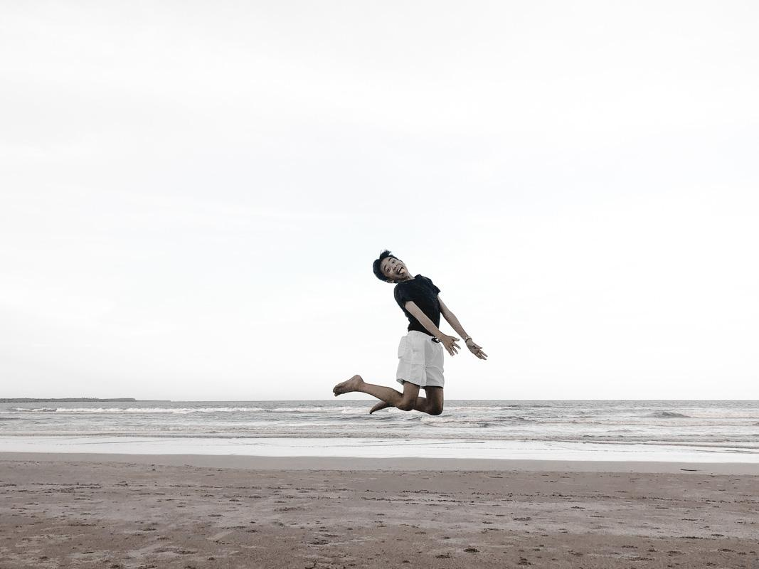 young boy jumping on the beach funny beach instagram captions