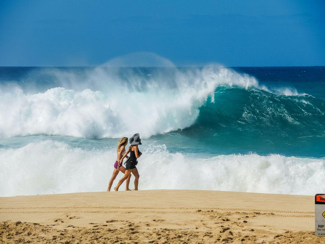 2 women walking on the beach with big wave a walk on the beach quotes