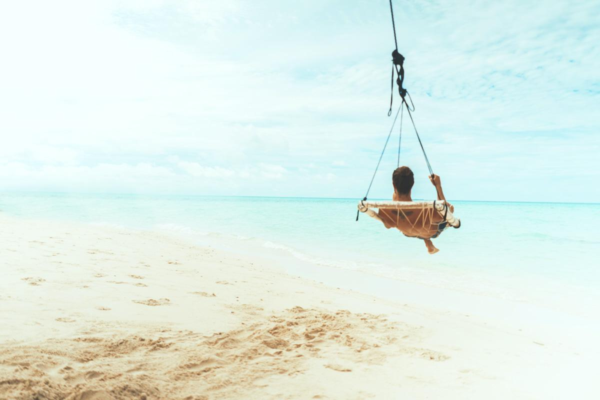 man swinging in hammock at the beach life quotes on beach life