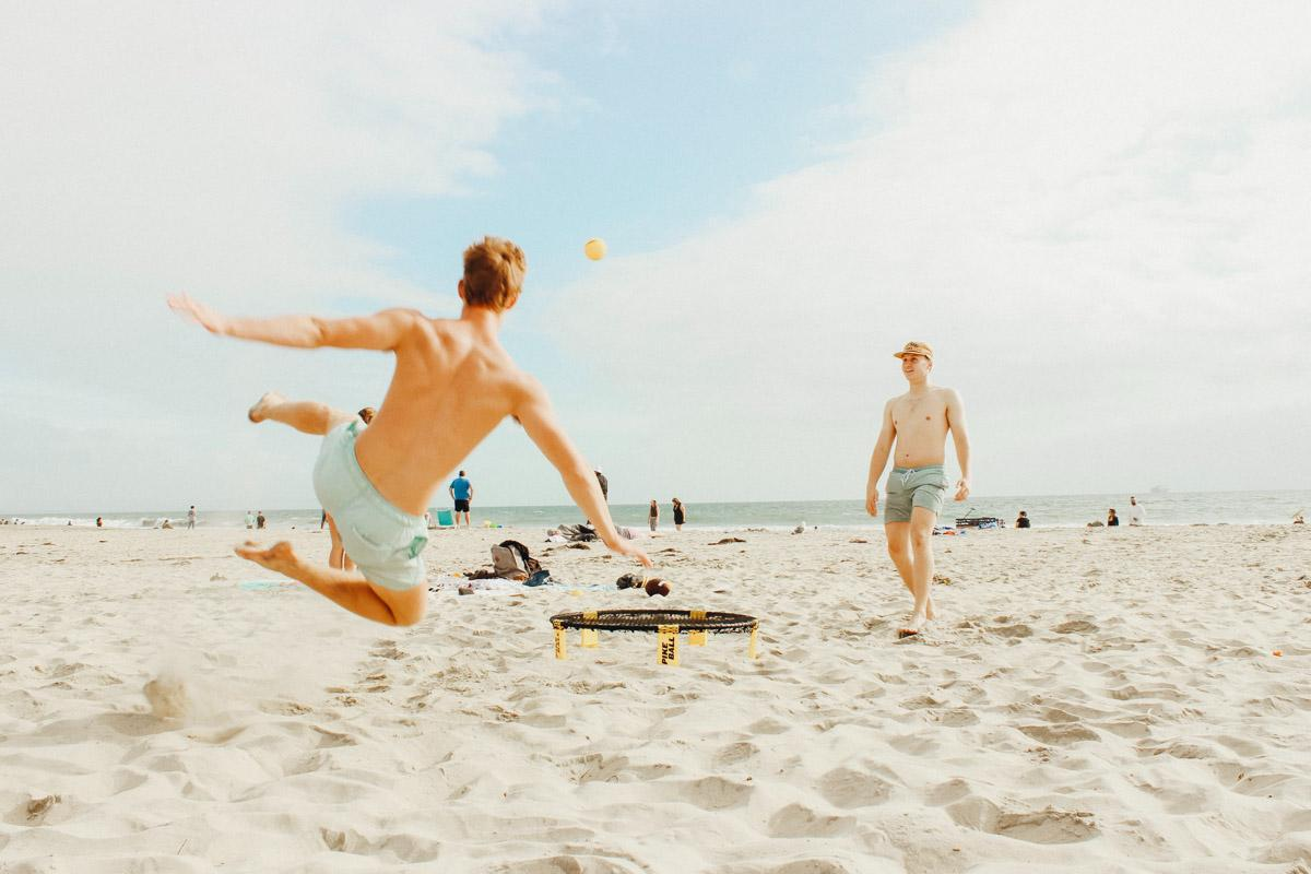 2 guys playing ball on the beach captions with friends