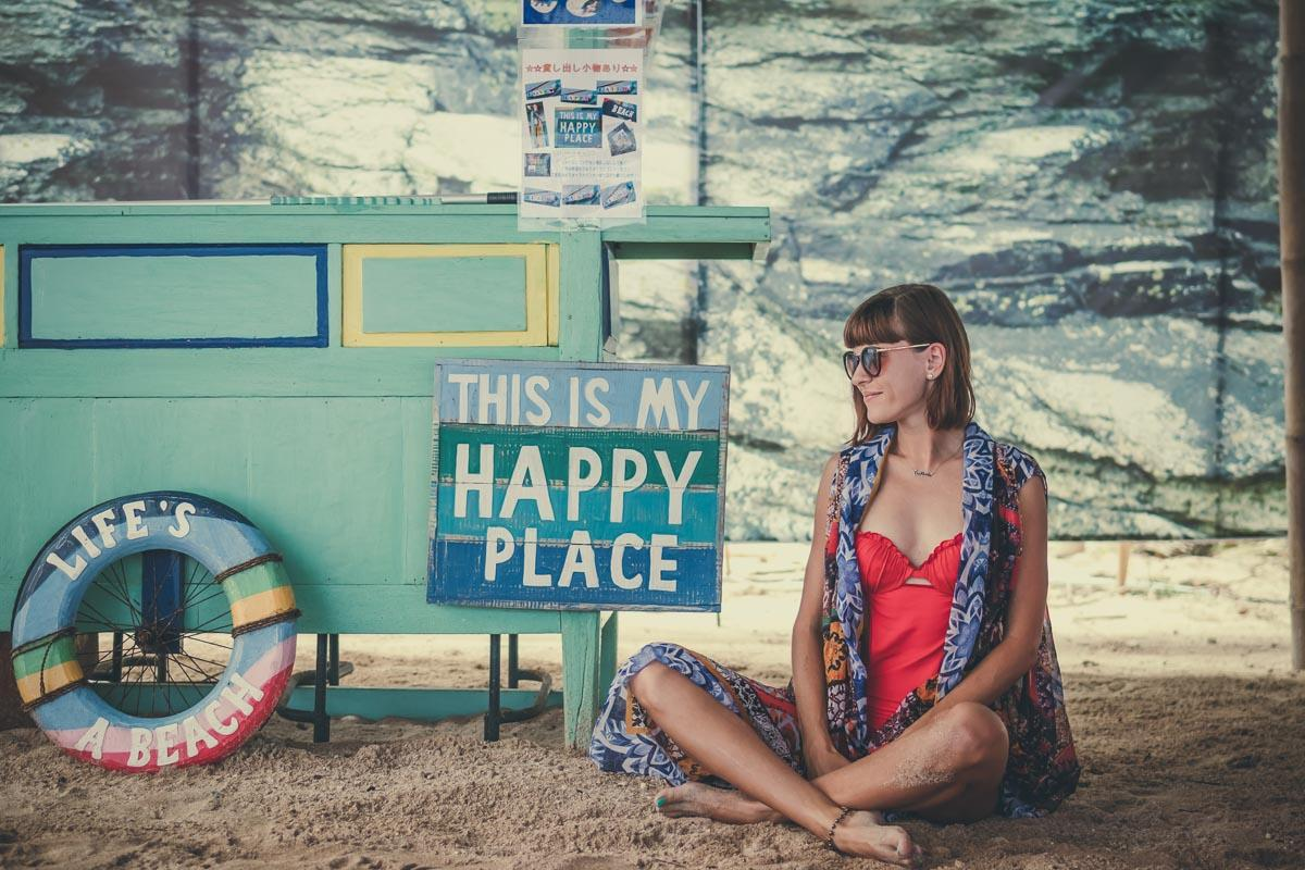 girl with happy place sign at the beach quotes