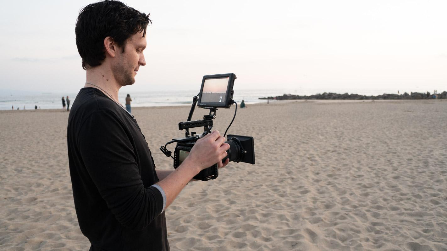 man with camera on the beach caption for instagram